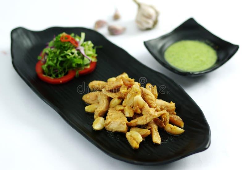 Pollo senz'ossa arrostito con aglio ed insalata sul vassoio nero immagini stock