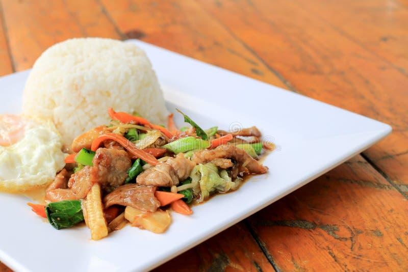 Pollo tailandés delicioso del plato con las verduras sofritas en el plato blanco con arroz y el huevo frito en la tabla de madera imagen de archivo