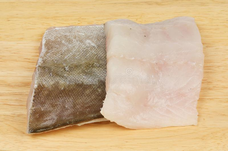 Pollock fish fillets. On a wooden chopping board royalty free stock photography