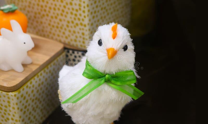 Polluelo decrative blanco de mirada arrogante de pascua con el arco verde con las cestas y conejito del juguete en el fondo - sit fotos de archivo