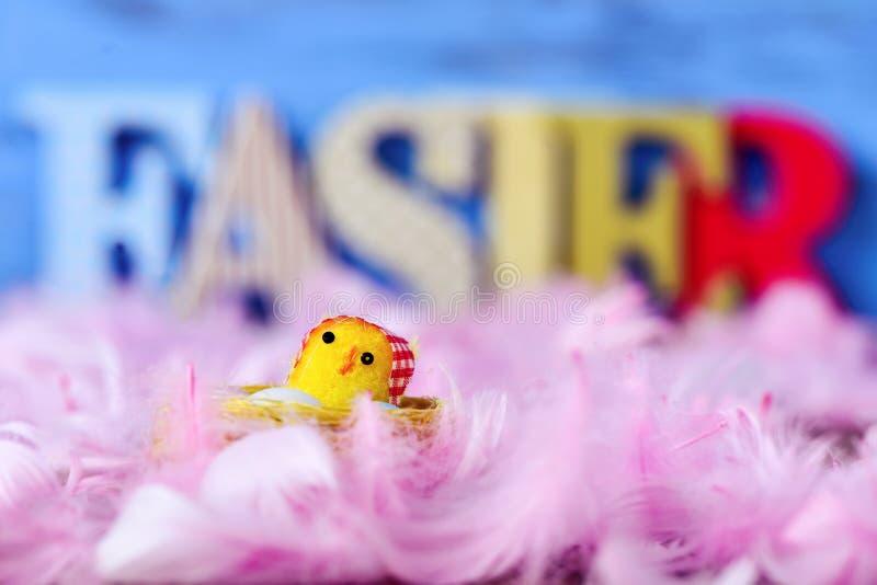 Polluelo del juguete, plumas y palabra pascua imagen de archivo
