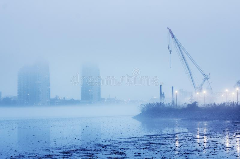 A polluted and foggy river in an industrial section. A lone crane shrouded in fog in an industrial section of a city alongside a polluted river stock photography