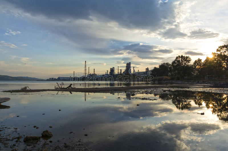 Polluted river. View of a polluted river mouth and an oil and gas plant at the background royalty free stock photo