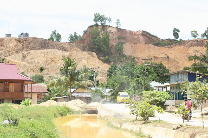 Polluted Water Canal in Sorong. Portrait of polluted water ditch among the family houses caused by mining activity from the hill (Sorong, West Papua, Indonesia royalty free stock photo