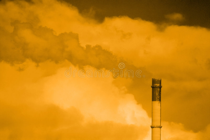 Polluting Chimney Stack. An industrial chimney stack belching out polluting smoke, in a sickly chemical yellow color stock photos