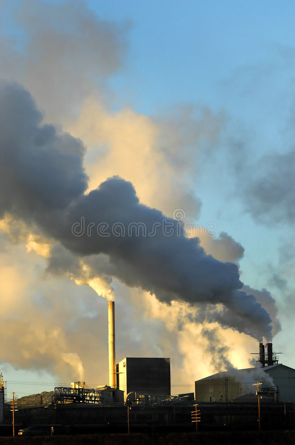 Pollution. Smokestacks from a factory spewing smoke and pollution into the air stock photos