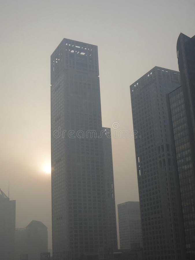 Pollution in Beijing -- Sun Shinning in Smoggy Haze Behind Skyscraper royalty free stock photos