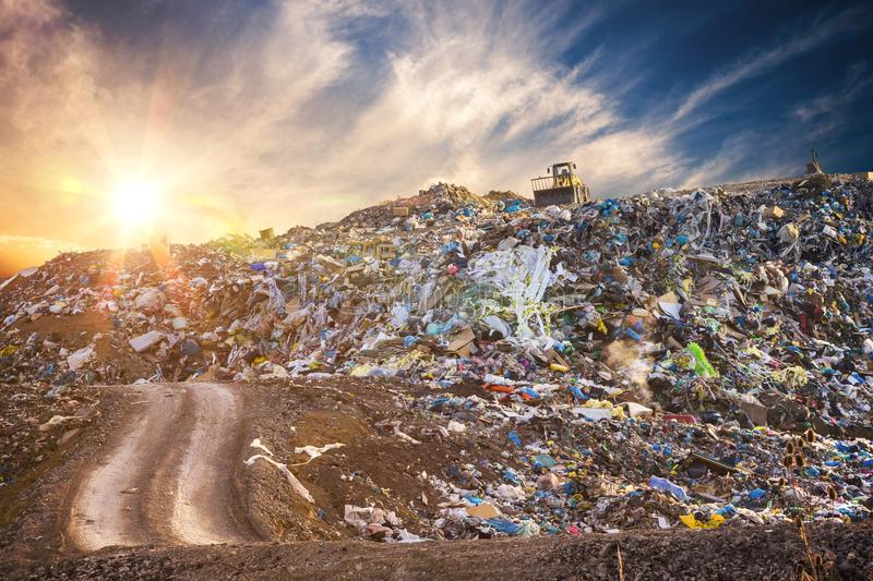 Pollution concept. Garbage pile in trash dump or landfill at sunset stock image