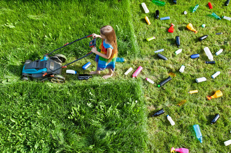 Pollution concept with little girl and plastic litter stock photography