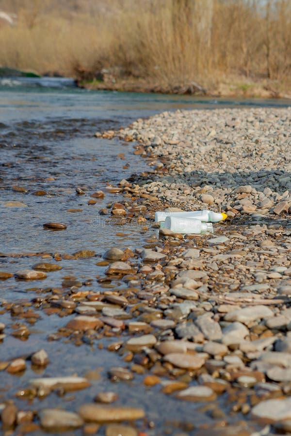 Pollution de rivière près du rivage, déchets près de la rivière, déchets alimentaires en plastique, contribuant à la pollution photos libres de droits