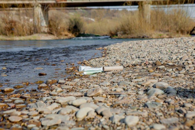Pollution de rivière près du rivage, déchets près de la rivière, déchets alimentaires en plastique, contribuant à la pollution image stock