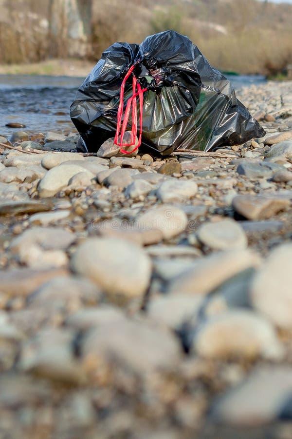 Pollution de rivière près du rivage, paquet de déchets près de la rivière, déchets alimentaires en plastique, contribuant à la po photos stock