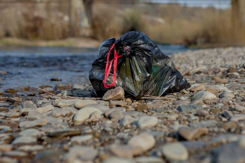 Pollution de rivière près du rivage, paquet de déchets près de la rivière, déchets alimentaires en plastique, contribuant à la po photos libres de droits
