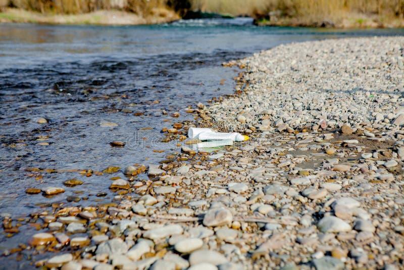Pollution de rivi?re pr?s du rivage, d?chets pr?s de la rivi?re, d?chets alimentaires en plastique, contribuant ? la pollution images libres de droits