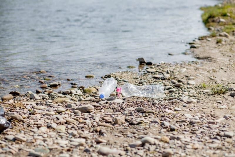 Pollution de rivi?re pr?s du rivage, d?chets pr?s de la rivi?re, d?chets alimentaires en plastique, contribuant ? la pollution images stock