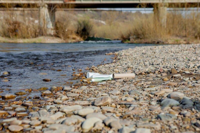 Pollution de rivi?re pr?s du rivage, d?chets pr?s de la rivi?re, d?chets alimentaires en plastique, contribuant ? la pollution image stock