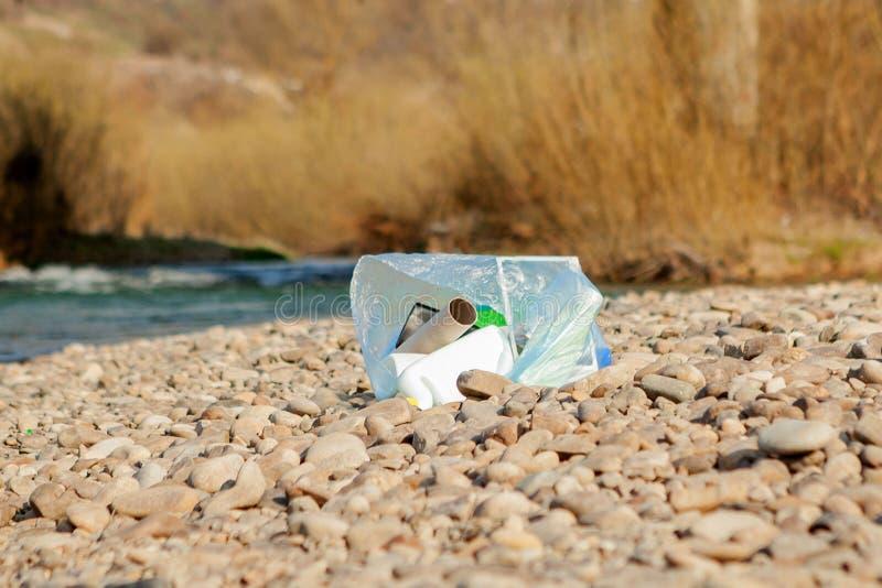 Pollution de rivi?re pr?s du rivage, d?chets pr?s de la rivi?re, d?chets alimentaires en plastique, contribuant ? la pollution photographie stock libre de droits