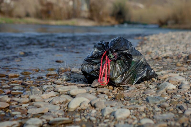 Pollution de rivi?re pr?s du rivage, paquet de d?chets pr?s de la rivi?re, d?chets alimentaires en plastique, contribuant ? la po photo stock