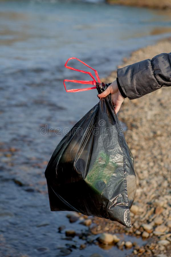 Pollution de rivi?re pr?s du rivage, paquet de d?chets pr?s de la rivi?re, d?chets alimentaires en plastique, contribuant ? la po image libre de droits