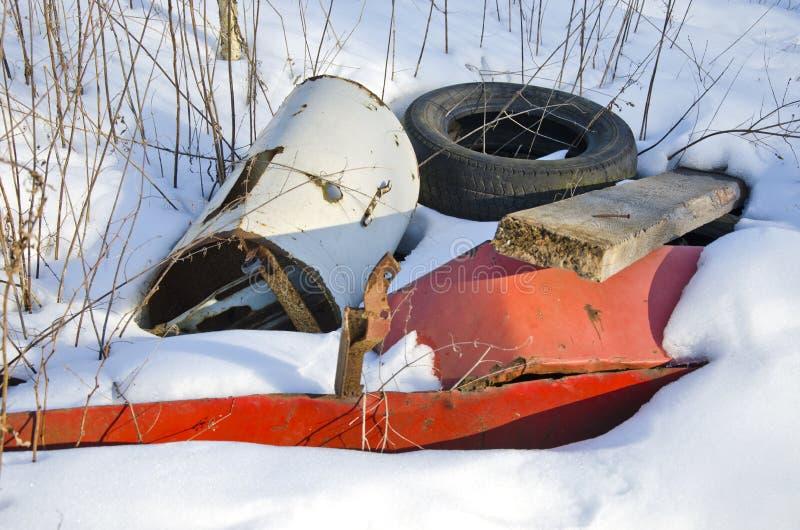 Pollution en métal et en caoutchouc sur la neige d'hiver photo stock