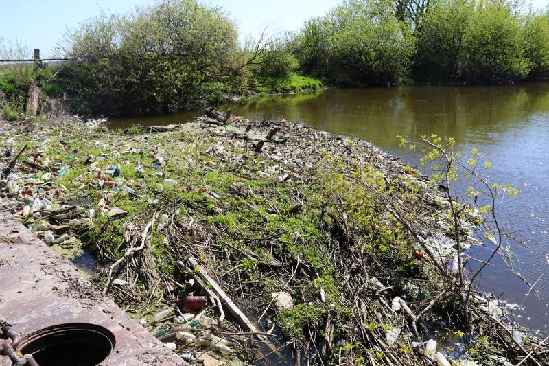 Pollution of the environment is a bunch of rubbish on the river bank stock image