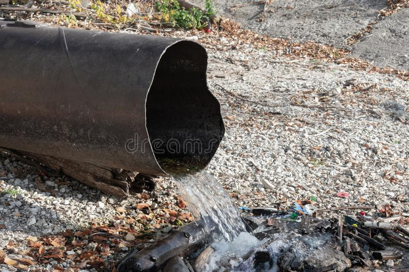 Discharge of toxic or contaminated water into a river or lake. Pollution of the environment by waste from pipes or drainage. The concept of nature pollution stock photography