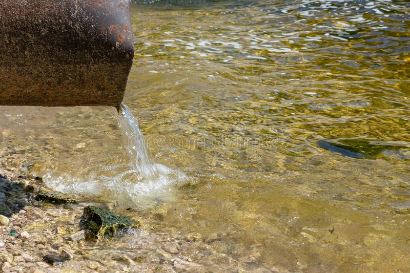 Discharge of toxic or contaminated water into a river or lake. Pollution of the environment by waste from pipes or drainage. The concept of nature pollution royalty free stock photos