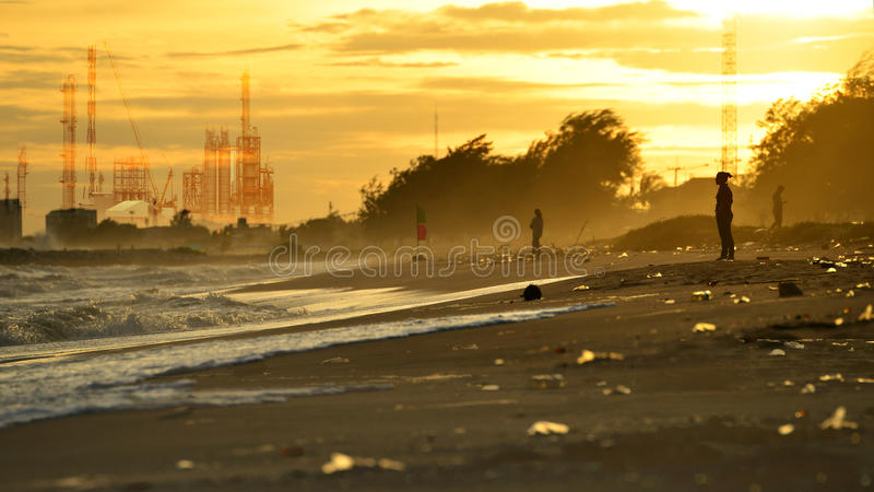 Pollution industry concept , Beach pollution. Plastic bottles and other trash on sea beach and Factory pipe polluting air against royalty free stock photo