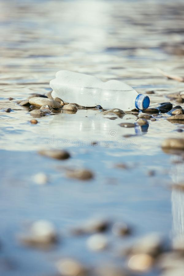 Environmental pollution: plastic bottle on the beach. Pollution waste plastic environmental protect bottle litter cleanup garbage trash water sea beach pvc pet stock images
