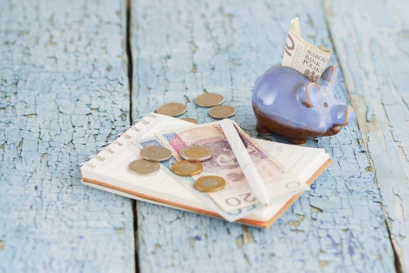 Polnischer Zloty, Sparschwein und Notizbuch auf dem hölzernen Hintergrund lizenzfreie stockfotos