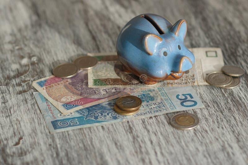 Polnischer Zloty und Sparschwein auf dem hölzernen Hintergrund stockfotos