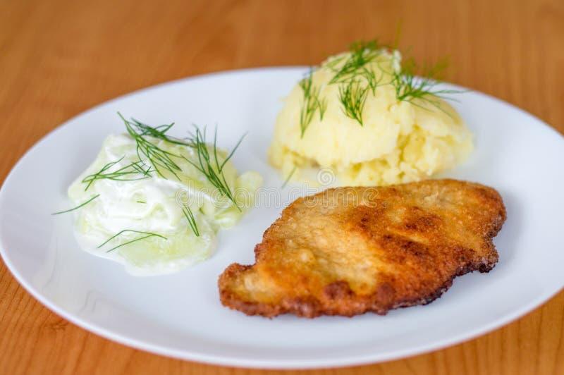 Polnisches kotlet schabowy Schweinekotelett mit mizeria und Kartoffelpürees lizenzfreie stockfotos