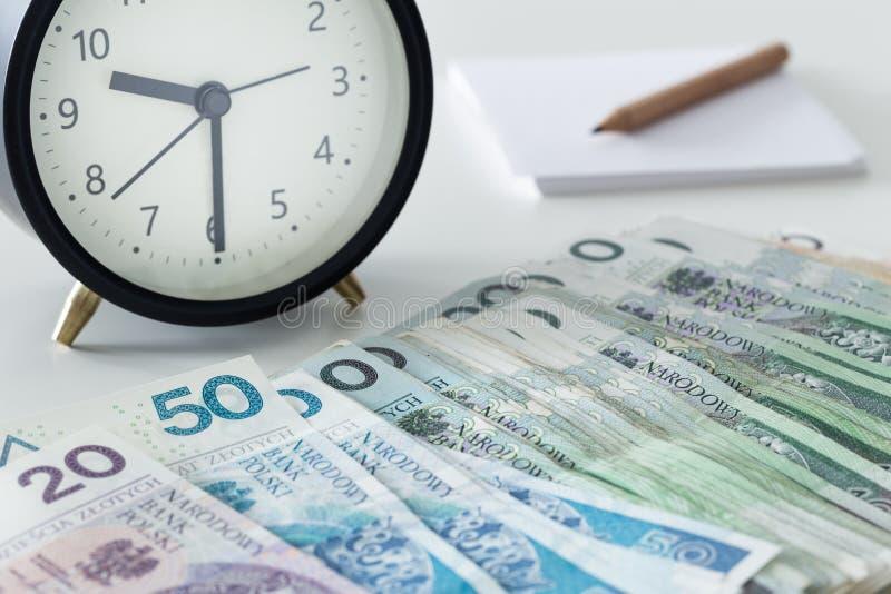 Polnisches Zlotygeld mit einem Wecker, einer Seite und einem Bleistift stockfoto
