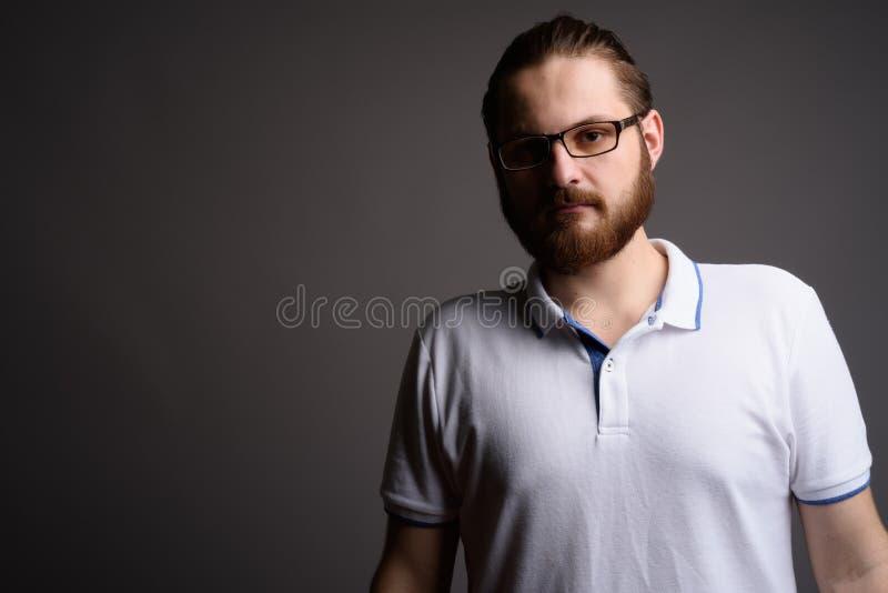 Polo blanc de port de jeune homme barbu contre le backgrou gris photo stock