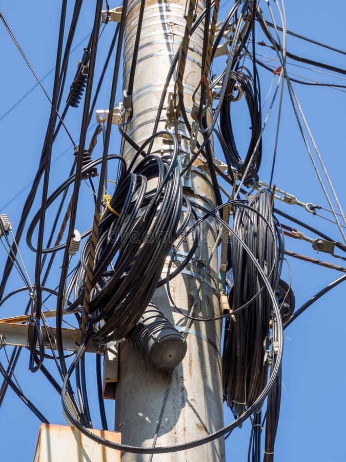 Polo concreto con las bobinas de una reserva de un cable de teléfono imagen de archivo
