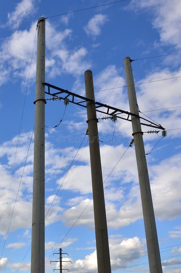 Polo concreto con los alambres de la línea eléctrica contra la perspectiva de SK nublada azul foto de archivo libre de regalías
