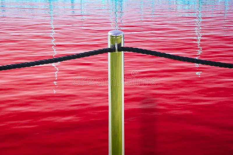 Polo cromado metal com corda preta no fundo vermelho foto de stock