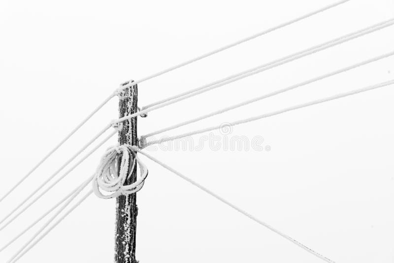 Polo da corrente elétrica com fios na geada do inverno imagens de stock royalty free