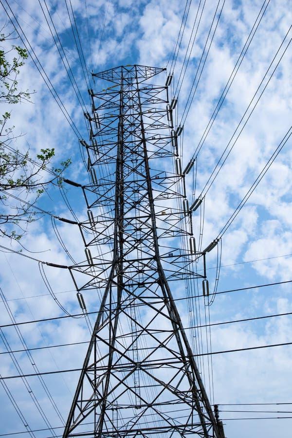 Polo de alta tensão no fundo bluesky, abastecimento de energia pela linha elétrica foto de stock royalty free