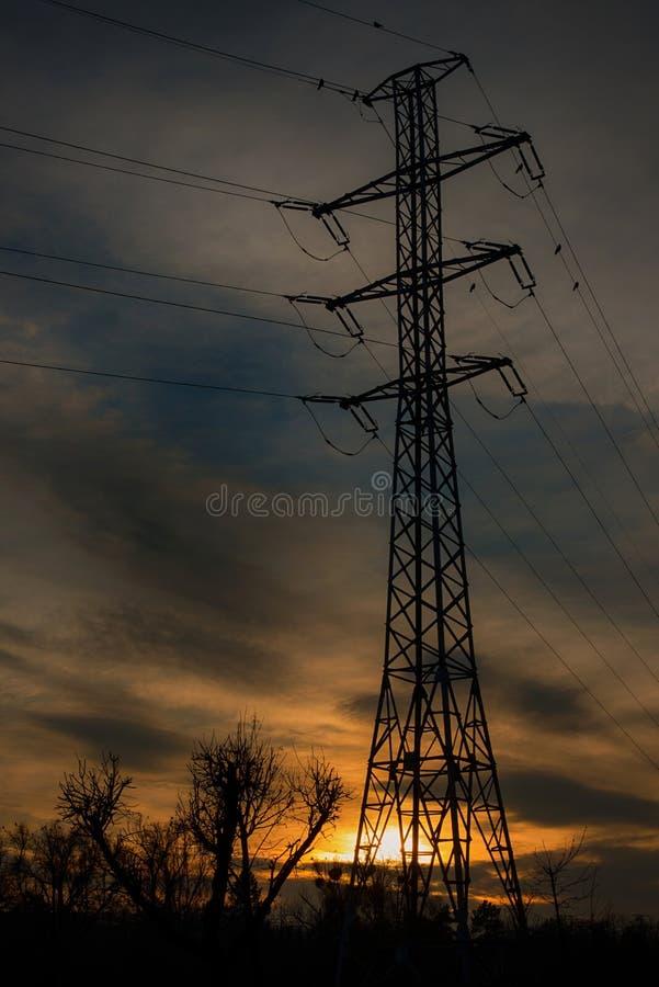 Polo de alto voltaje en puesta del sol imagenes de archivo
