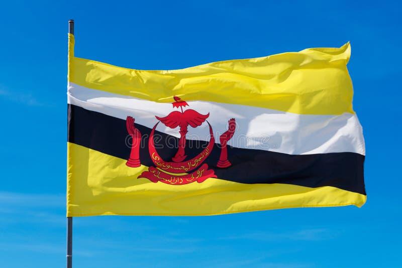 Polo de bandeira de Brunei Darussalam no fundo do céu fotos de stock