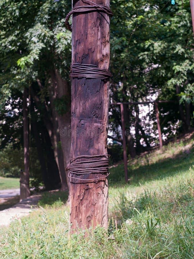 Polo de madera oxidado eléctrico viejo envuelto en alambre de metal foto de archivo
