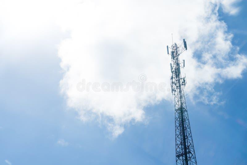 Polo del transmisor del teléfono móvil en el cielo azul y las nubes imagen de archivo