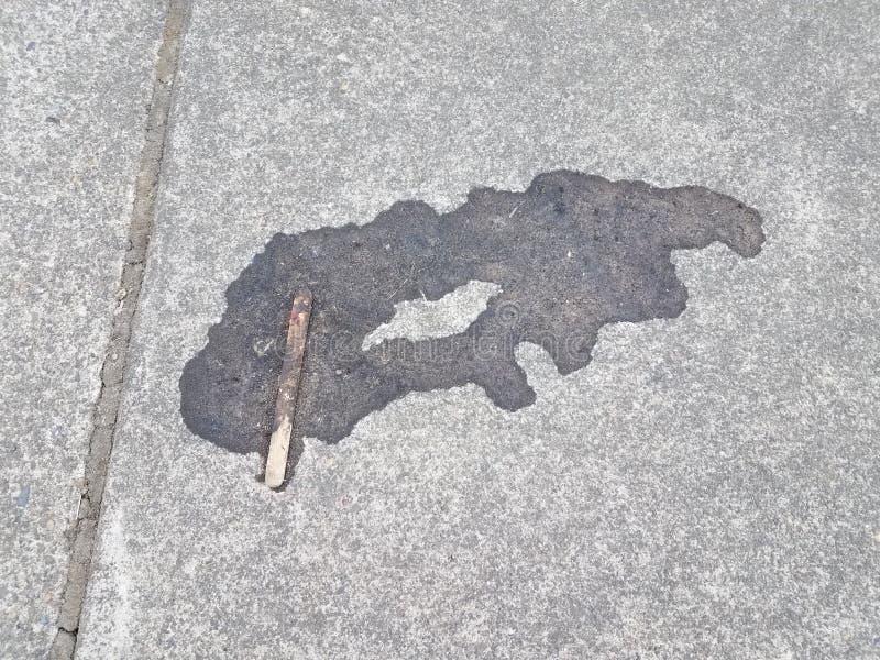 Polo derretido con el palillo en el cemento gris imagenes de archivo