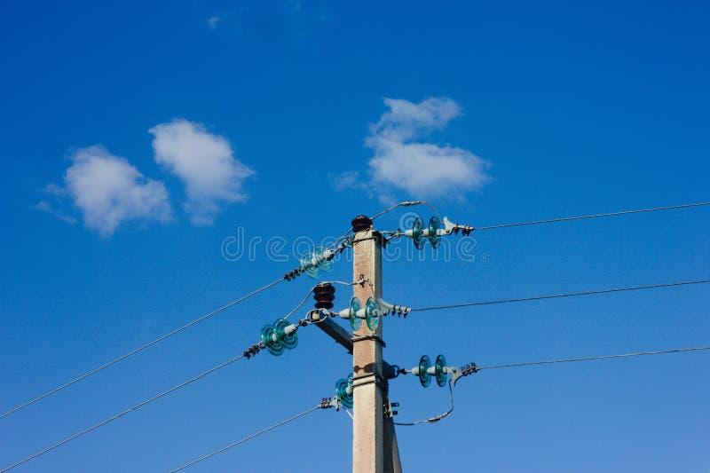 Polo eléctrico contra el cielo azul con el pájaro que oculta dentro fotografía de archivo