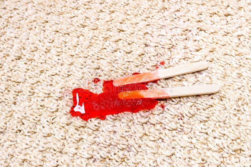 Polo rojo que derrite en la alfombra fotos de archivo