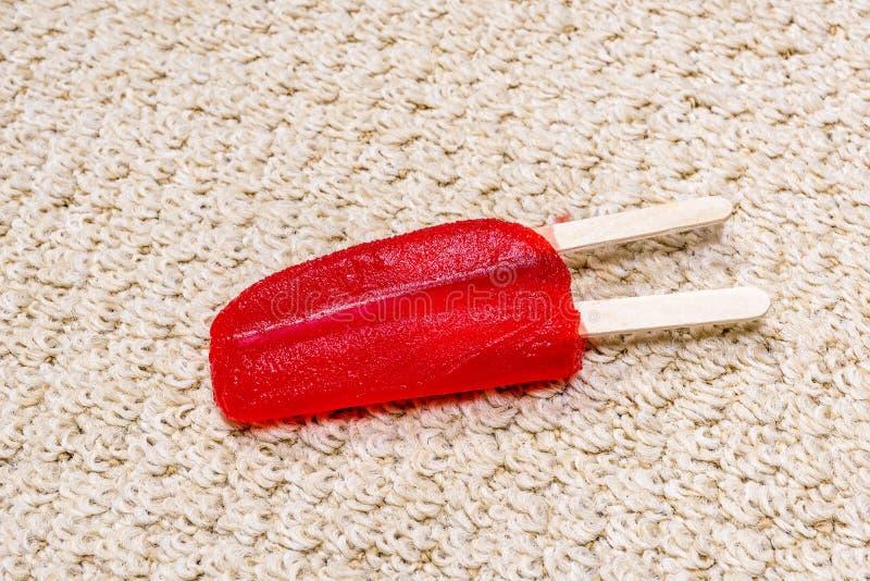 Polo rojo que derrite en la alfombra imagen de archivo