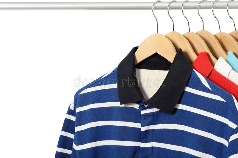 Polo shirts. Colorful polo shirts on hangers isolated royalty free stock photos