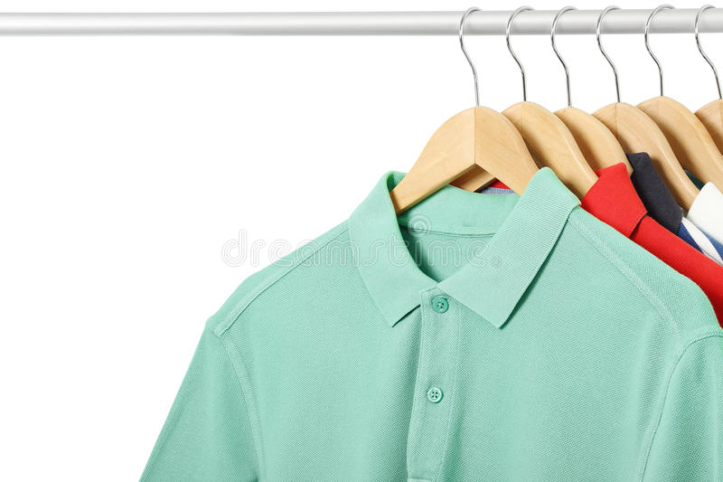 Polo shirts. Variety of polo shirts on hangers isolated stock photography