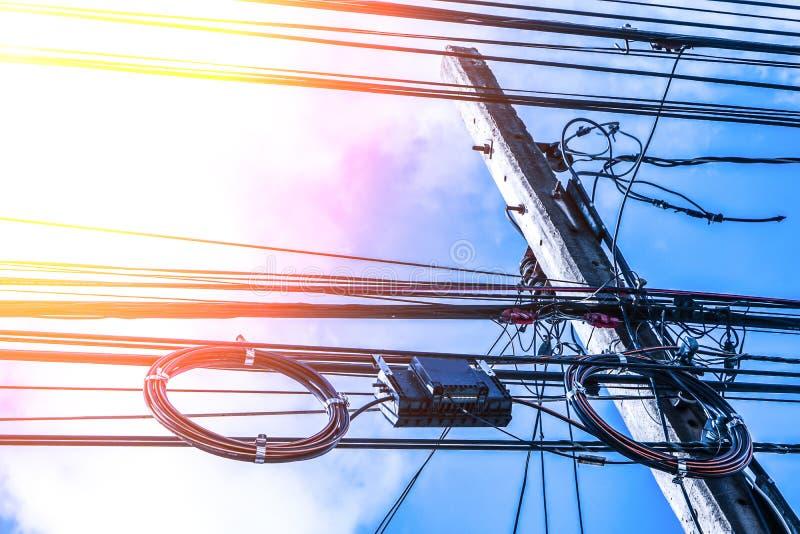 Polo y línea eléctrica de alto voltaje de la electricidad del transformador con el fondo azul de cielo nublado imagen de archivo libre de regalías